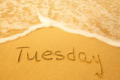 Tuesday - written in sand on beach texture. — Stock Photo