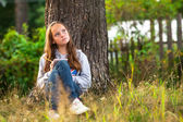 Teen-girl writing in a notebook while sitting in park. — Stock Photo