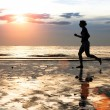 Silhouette of a young woman jogger at sunset on seashore — Stock Photo #24813121