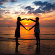 Couple holding hands heart-shaped on the sea beach at sunset — Lizenzfreies Foto