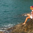 Girl is sitting on the rocks at the seaside — ストック写真