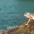 Foto Stock: Girl is sitting on the rocks at the seaside