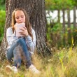 Girl writing in a notebook while sitting in the park — Stock Photo