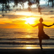 Young woman practicing yoga at sunset on the coast of Ko Chang island, Thailand — Stock Photo #24813411