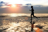 Silhouette of a young woman jogger at sunset on seashore — Stock Photo