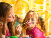 Young funny two sisters playing with painting — Stock Photo