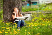 Teengirl in the park with books — Stock Photo