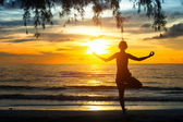 Young woman practicing yoga at sunset on the coast of Ko Chang island, Thailand — Stock Photo