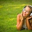 Happiness girl with headphones enjoying nature and music at sunny day. — Stockfoto