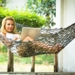Stock Photo: Girl lies in hammock with laptop.