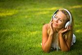 Szczęście dziewczyna ze słuchawkami zachwyt przyrodą i muzyki w słoneczny dzień. — Zdjęcie stockowe