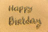 Inscription Happy Birthday on texture of sand. — Stock Photo