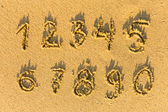Numbers (from one to ten) written on a sandy beach — Stockfoto