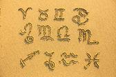 Zestaw znaków zodiaku - na piasku plaży dokumentu faktury. — Zdjęcie stockowe
