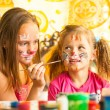 Stock Photo: Sisters playing with painting