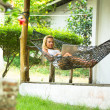 Young girl lies in the hammock with laptop. — Stok fotoğraf