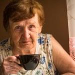 Old woman is drinking tea — Stock Photo #25880451