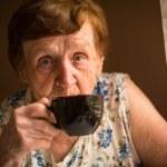 yaşlı bir kadın evinde çay içiyor — Stok fotoğraf