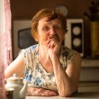 An elderly woman at her home — Stockfoto