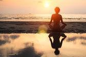 Yoga vrouw op een strand — Stockfoto