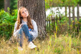 Teenage girl with notebook in park — Stock Photo