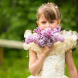 Portrait of a little girl with a bouquet of lilacs outdoors — Stock Photo
