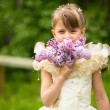 Portrait of a little girl with a bouquet of lilacs outdoors — Stock Photo #26165071