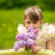 Portrait of a little girl with a bouquet of lilacs — Stock Photo