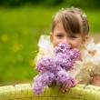 Little lovely girl with a bouquet of lilacs outdoors — Stok fotoğraf