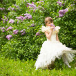 Stock Photo: Little lovely girl with a bouquet of lilacs sitting on a bench in the garden