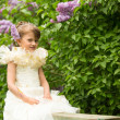 Little lovely girl sitting on a bench in the garden — Stock Photo