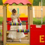Little lovely girl in an elegant dress on the playground — Stock Photo