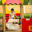 Baby girl in an elegant dress on the playground — Stock Photo #26166133