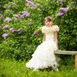 Lovely girl sitting on a bench in the garden. — Foto Stock