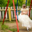 Little lovely girl on a swing in playground — Stock Photo #26166435