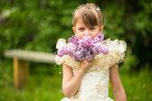 Porträtt av en liten flicka med en bukett av syrener utomhus — Stockfoto