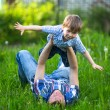 Foto Stock: Father and son playing lying on the grass in the park