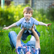 Father and son playing in the park lying on the grass — Stock Photo #26855179