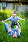 Father and son playing in the park lying on the grass — Stock Photo