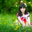 Beautiful teengirl sitting in the grass — Stockfoto