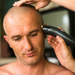 Close-up: Hairdresser shaving man with hair trimmer. — ストック写真