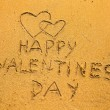 In the beach sand: Happy Valentine's Day and two hearts — Stock Photo #27462957