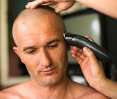 Close-up: Hairdresser shaving man with hair trimmer. — Stock Photo
