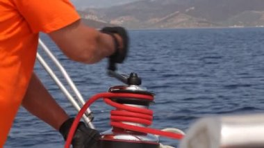Man sailing, man pulling ropes, winding sheets around winches — Stock Video