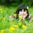 Pretty young girl lying in the grass in the park — Stock Photo