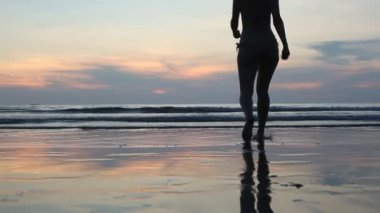 A young woman walks into the sea at sunset, backlit — Stock Video #27522085
