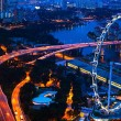 Aerial view on Singapore Flyer from roof Marina Bay Hotel at night. — Foto de Stock