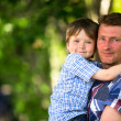 Foto Stock: Portrait of father and son in the park