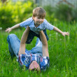 Стоковое фото: Father playing in grass with his small son
