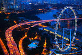 Aerial view on Singapore Flyer from roof Marina Bay Hotel at night. — Stok fotoğraf